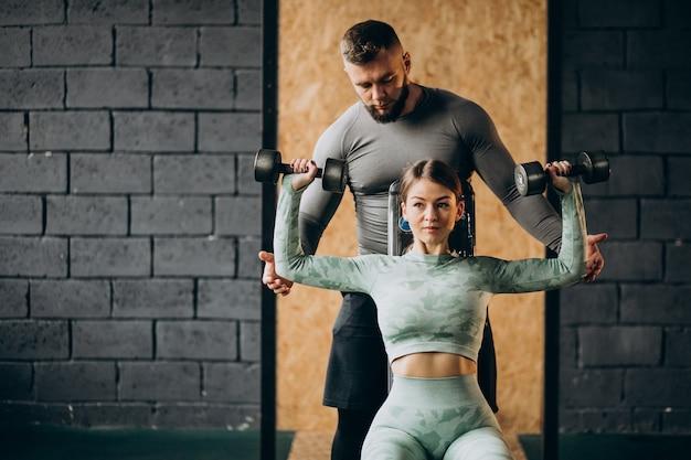 Frau, die training im fitnessstudio mit trainer macht