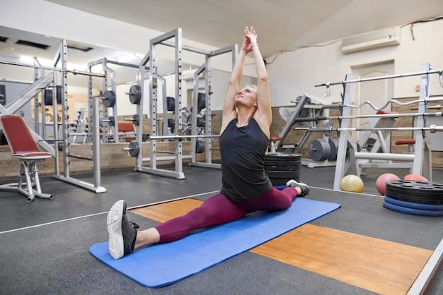 Frau, die training in der turnhalle, übendes yoga der frau ausdehnend tut