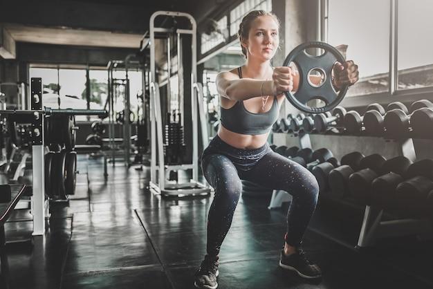 Frau, die training mit gewichtsplatte an der turnhalle tut