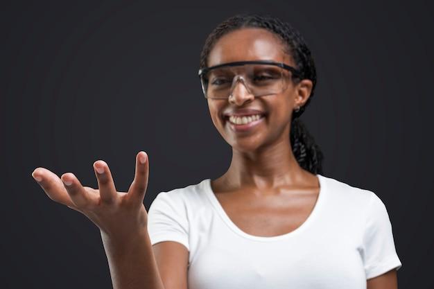 Frau, die transparente brille trägt, die unsichtbares objekt zeigt