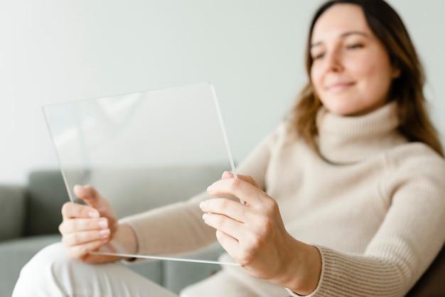 Frau, die transparente tablette auf einer couch innovative technologie verwendet