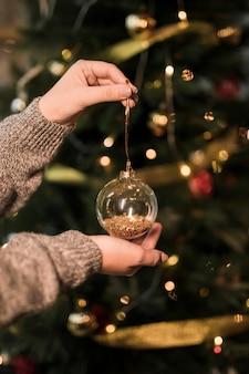 Frau, die transparenten weihnachtsball der verzierung hält