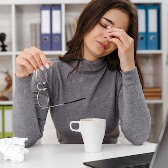 Frau, die traurig schaut, während sie von zu hause aus arbeitet
