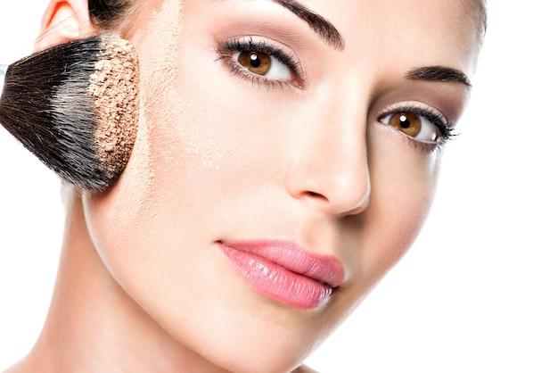 Frau, die trockene kosmetische tongrundierung auf gesicht mit make-up-pinsel aufträgt.