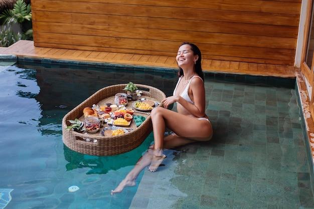 Frau, die tropisches gesundes frühstück an der villa auf schwimmendem tisch hat