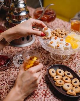 Frau, die türkische freude mit schwarzem tee mit zitrone hat