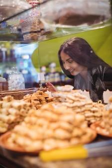 Frau, die türkische süßigkeiten im geschäft betrachtet