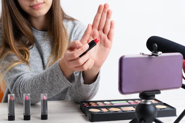 Frau, die tut, tut kosmetisches make-up-tutorial-blog mit make-up-farben, die kamera betrachten, die sie auf dem sozialen internet der sozialen medien online teilt