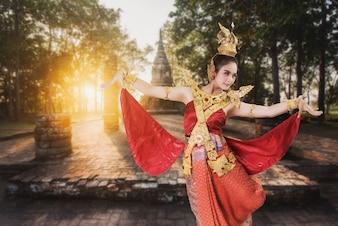 Frau, die typisches thailändisches Kleid auf altem Tempelhintergrund trägt