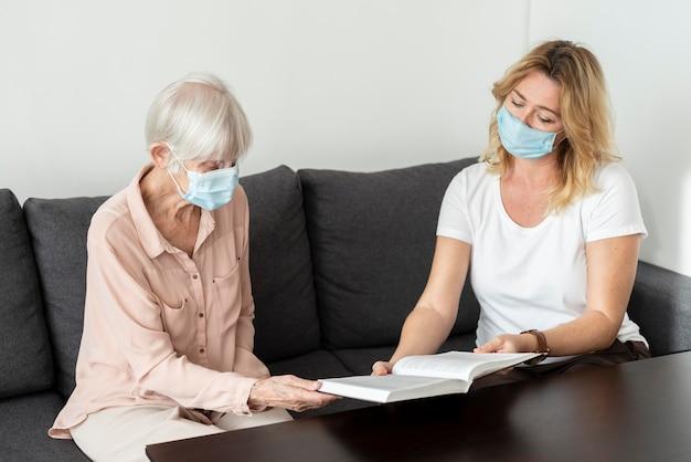 Frau, die über buch mit älterer frau am pflegeheim spricht