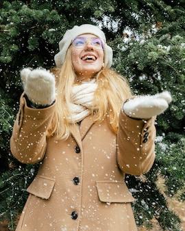 Frau, die über den schneefall am park im winter glücklich ist
