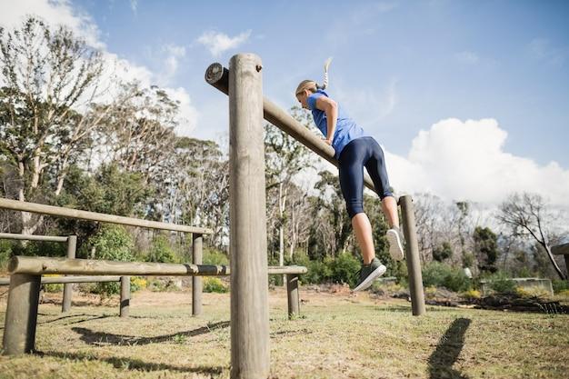 Frau, die über die hürden während des hindernislaufs im bootcamp springt