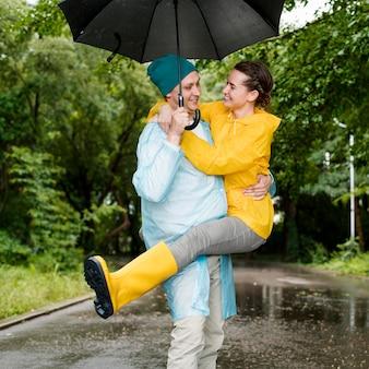 Frau, die über ihren ehemann unter dem regenschirm springt