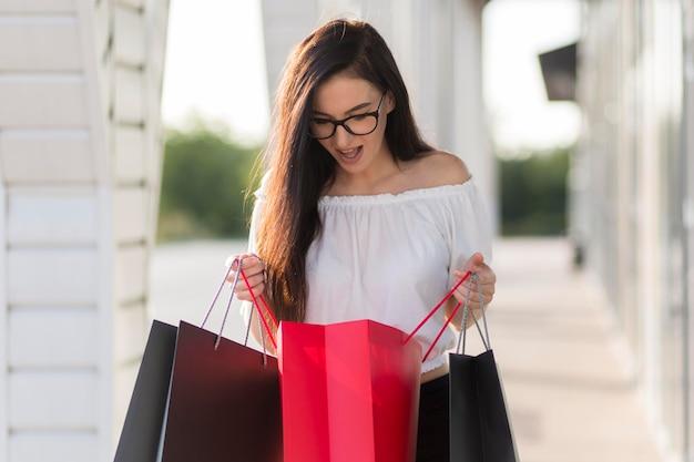 Frau, die überrascht ist und in einkaufstaschen schaut