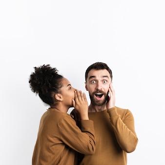 Frau, die überraschtem mann ein geheimnis erzählt