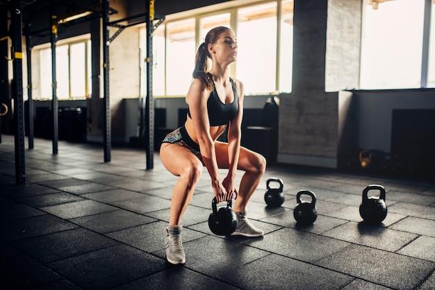 Frau, die übung mit gewicht im fitnessclub tut