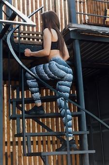 Frau, die übungen auf treppenhaus tut