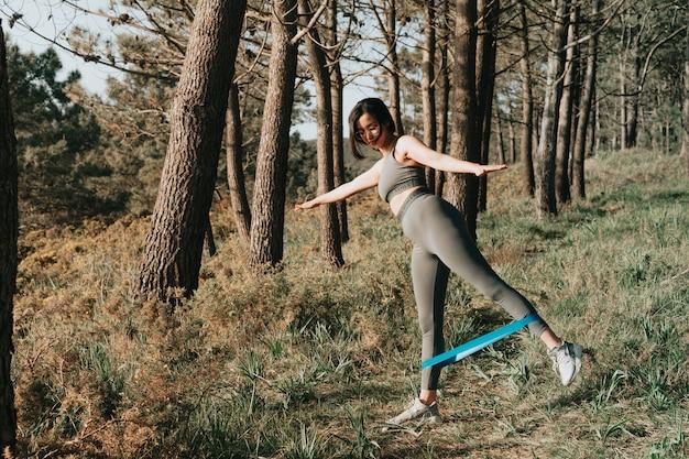 Frau, die übungen im wald mit einem gummiband macht