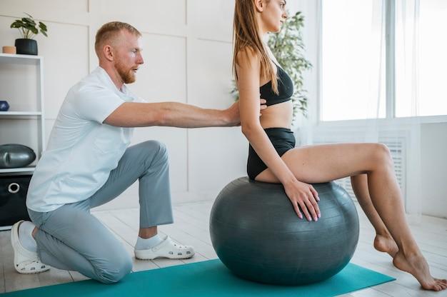 Frau, die übungen mit ball und physiotherapeut macht