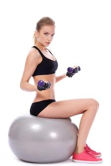 Frau, die übungen mit dummköpfen auf eignungsball tut