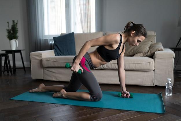 Frau, die übungen mit gewichten auf yogamatte tut
