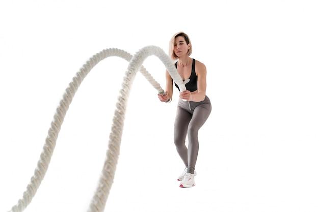 Frau, die übungen mit kampfseil auf weiß macht