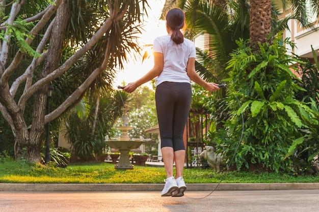 Frau, die übungen mit springendem seil zu hause macht.