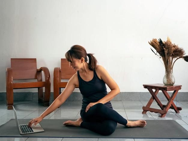 Frau, die übungsanzug trägt, auf yogamatte sitzt, laptop für suchklasse für dehnungskörper verwendet, aktivität zu hause macht.