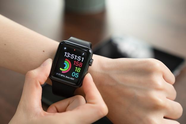 Frau, die uhr berührt. digitaluhr, die für viele funktionen verwendet werden kann.