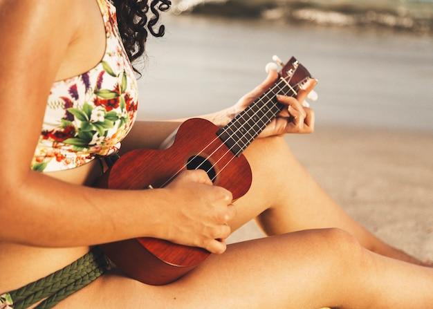 Frau, die ukulele am strand spielt