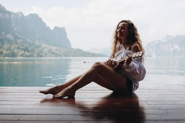 Frau, die ukulele durch das wasser spielt