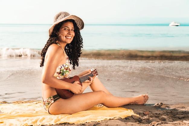 Frau, die ukulele durch meer spielt