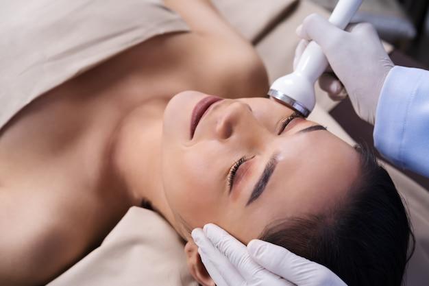 Frau, die ultraschallgesichtsschönheitsbehandlungs-hautpflege empfängt