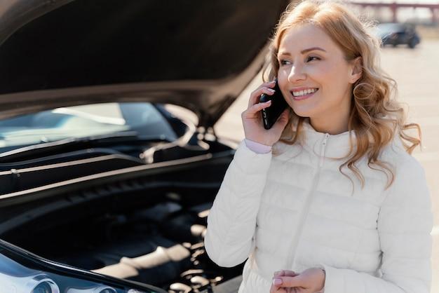 Frau, die um hilfe für ihr auto ruft