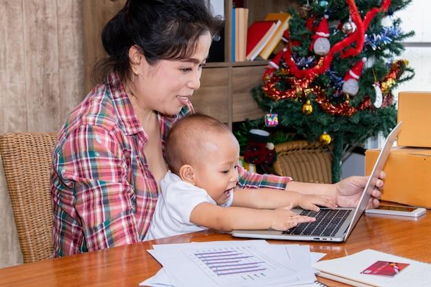 Frau, die um ihrem baby beim arbeiten im büro nahe dem weihnachtsbaum sich kümmert
