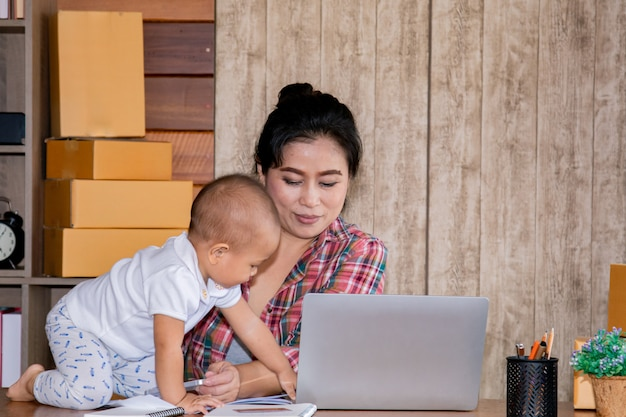 Frau, die um ihrem baby beim arbeiten im büro sich kümmert