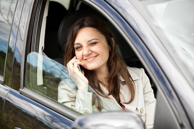 Frau, die um smartphone im auto ersucht.