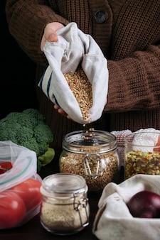 Frau, die umweltfreundliche und abfallfreie artikel verwendet, um frisches gemüse und getreide zu lagern.