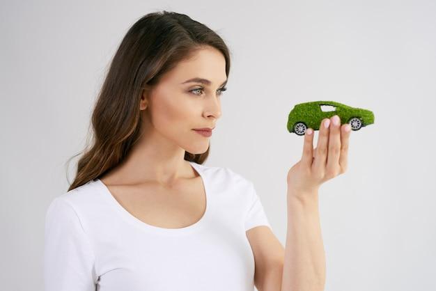 Frau, die umweltfreundliches auto betrachtet Premium Fotos