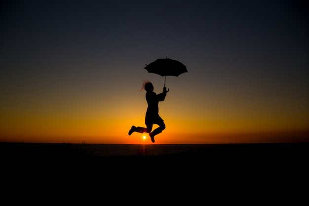 Frau, die und regenschirm in schattenbild gegen orange sonnenuntergang hält