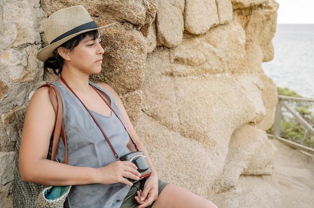Frau, die unendlichkeit vor dem meer mit einer kamera in ihren händen betrachtet