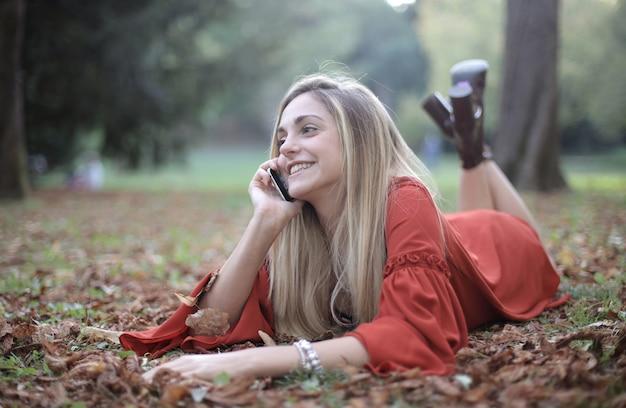 Frau, die unten auf dem waldboden liegt und am telefon spricht