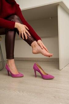 Frau, die unter beinschmerzen im amt leidet. sie rieb schreckliche schwielen von unbequemen schuhen mit hohen absätzen