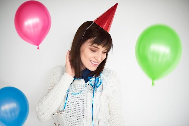 Frau, die unter bunten luftballons tanzt