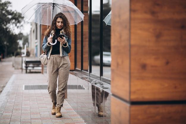 Frau, die unter dem regenschirm in einem regnerischen wetter geht