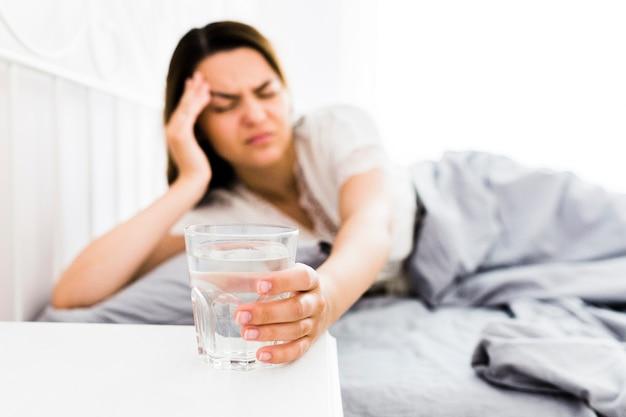 Frau, die unter den kopfschmerzen nehmen glas wasser leidet