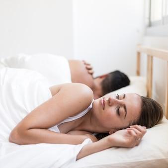 Frau, die unter der schlaflosigkeit liegt auf bett nahe ihrem ehemann leidet