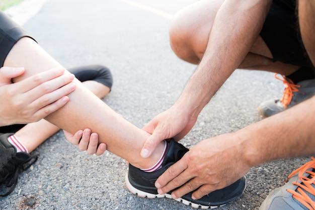 Frau, die unter einer knöchelverletzung beim trainieren leidet, sie erhält hilfe vom mann.