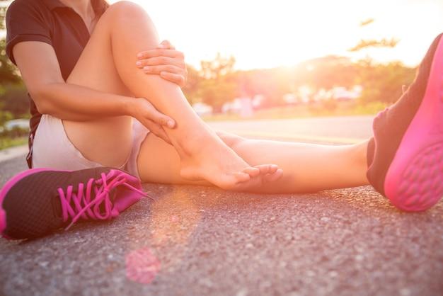 Frau, die unter einer knöchelverletzung beim trainieren leidet.