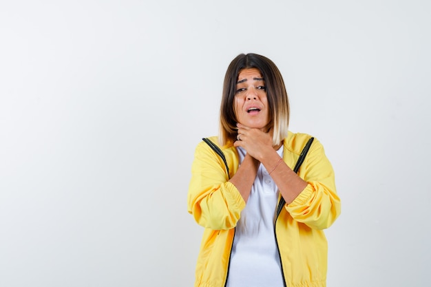 Frau, die unter halsschmerzen im t-shirt, in der jacke leidet und krank aussieht, vorderansicht.